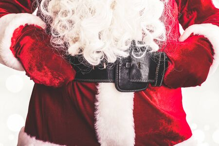 abdomen yellow jacket: Closeup of a red Santa Claus costume with belt and buckle