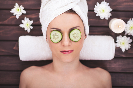 Beautiful girl at spa salon with cucumbers on eyes Stock Photo
