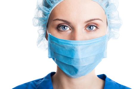 白で隔離キャップ、顔のマスクの若い女性医師 写真素材