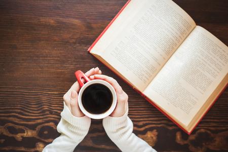 libros antiguos: Manos de la muchacha que sostiene la taza de café caliente en la mesa de madera