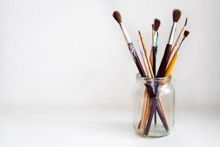 Tarro de cepillos de pintura en el fondo blanco