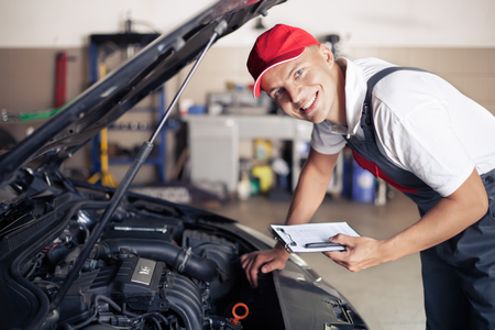 mecanico: Retrato de un mecánico tomando notas y sonriente