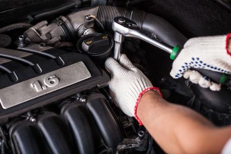 mantenimiento: Manos del mecánico de automóviles en el servicio de reparación de automóviles. Foto de archivo