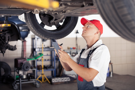 mot: Portrait of a mechanic taking notes under a car