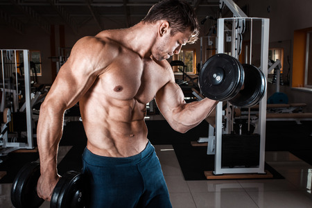 Man at the gym. Man makes exercises with dumbbells Stock Photo