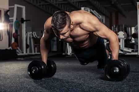 Stattlicher muskulöser Mann tun pushup Übung mit Hantel in einem CrossFit Training