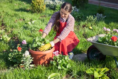 Junge Frau, die Blumen im Topf mit Schmutz oder Boden zu pflanzen. Gartenarbeit
