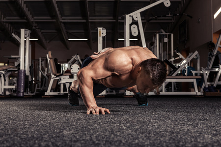Portrait of a muscular man doing push ups exercise with one hand in fitness gym