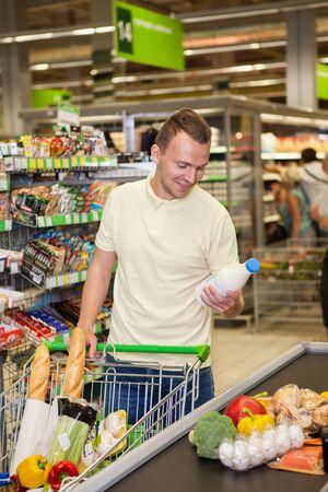 handsom: Handsom man buying products in a supermarket