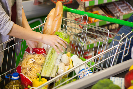 necessities: Full shopping cart at store with fresh products.