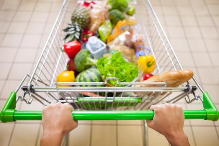 Homem com carrinho cheio de produtos na supermercado vista superior Imagens