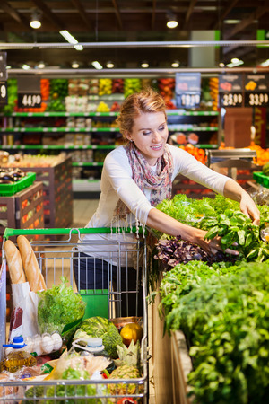 green leafy vegetables: Portrait of beautiful young woman choosing green leafy vegetables in grocery store. Concept of healthy food shopping