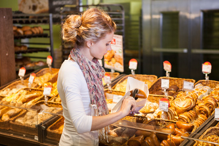 eating pastry: Young woman buying fresh bread in bakery