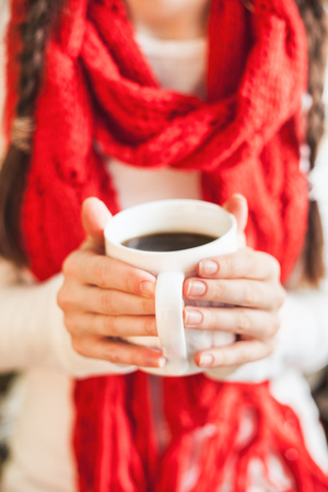 Woman holding a mug with hot coffee. Winter and Christmas time concept.