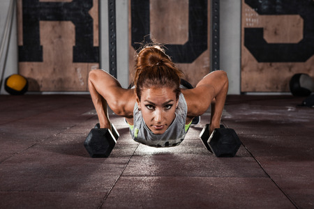 Woman doing push-up exercise with dumbbell. Strong female doing crossfit workout.