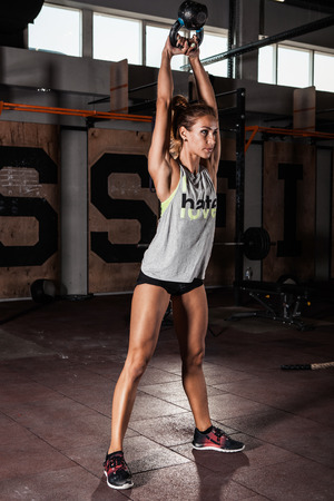 Attractive young athlete with muscular body exercising crossfit. Woman in sportswear doing crossfit workout