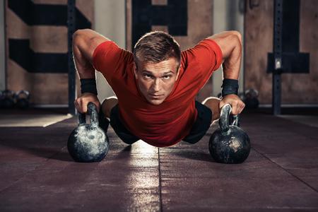 Knappe spier man doet push ups op ketel bal in de sportschool Stockfoto