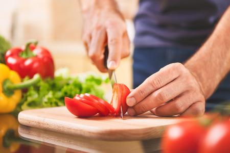 自宅のまな板に男手切削トマト料理、食品、ホーム コンセプト - アップします。