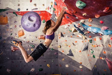 Free climber young woman climbing artificial boulder indoors