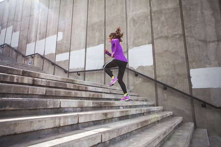 young sporty woman running upstairs on city stairs
