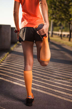 Young fitness woman runner stretching legs before run,  warm up outdoor. Sport lifestyle. Stock Photo