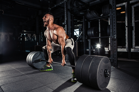 Muscular men lifting deadlift In the gym Stock Photo