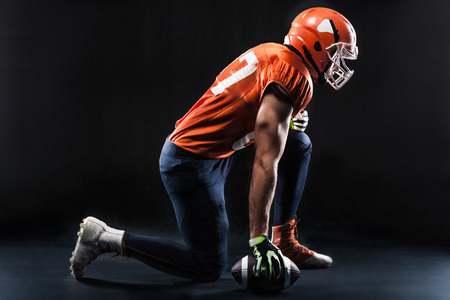 American football sportsman player ready for training on black background