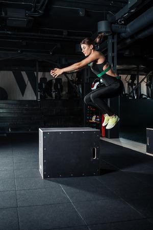 Junge Frau, die eine Boxsprungübung tut. Muskulöse Frau macht eine Box hocken in der Turnhalle Lizenzfreie Bilder