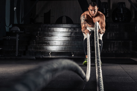 Athletic man doing some cross-training exercises with a rope in gym. Attractive muscular man working out with heavy ropes.