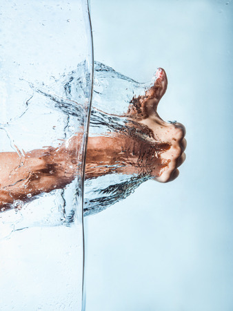 Woman Fist through the Blue Water and splashing drops,Like hand sign Stock Photo
