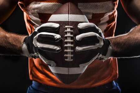 American football sportsman player  holding a ball on black background closeup