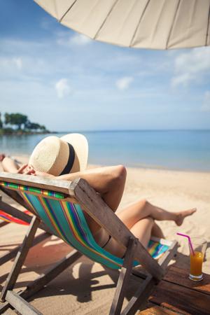 Woman at beautiful beach sitting on chaise-lounge