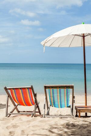 Vacation holidays background wallpaper - two beach lounge chairs under umbrella on beach. Standard-Bild