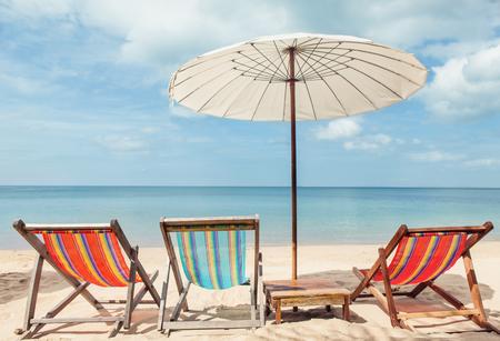 Vacation holidays background wallpaper beach lounge chairs under umbrella on beach. Standard-Bild