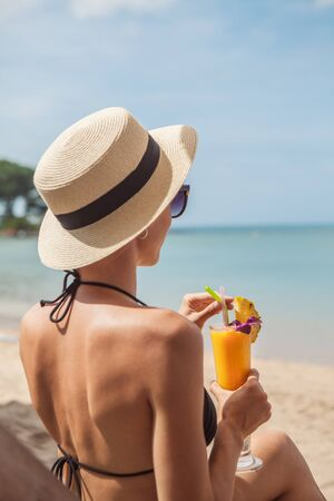 Woman holding fresh fruit cocktail on a tropical  beach
