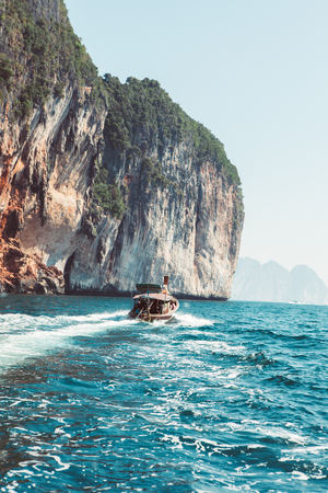 Travel vacation background with a touristic boat in front. Tropical island.