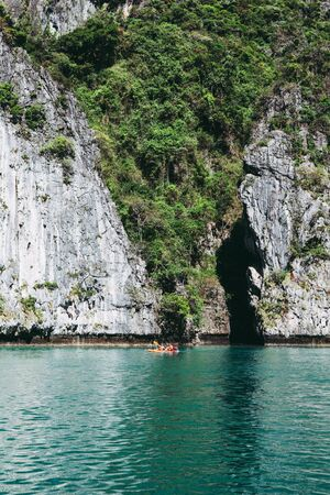 Tourists on a kayak  in front of the big rock in the tropics. Vacation holiday activity