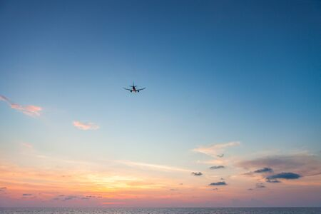 Airplane flying above sea at sunset
