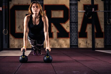 Life of fitness. Attractive young gym fitness woman doing push-ups with weights beautiful sportswoman doing crossfit workout pushup exercise with kettlebells copyspace sport lifestyle strength success