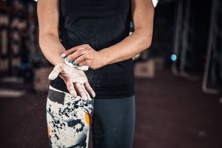 Girl getting ready for crossfit training. Woman athlete powerlifter to compete in deadlift. hands in chalk