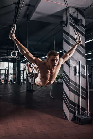 Muscle-up exercise athletic man doing intense workout at the gym on gymnastic rings