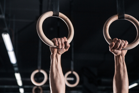 Young Male Athlete With Gymnastic Rings In The Gym. focus on rings