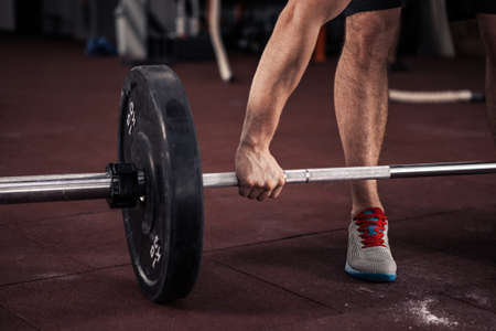 Hand on the barbell. Young athlete getting ready for weight lifting training Stock Photo