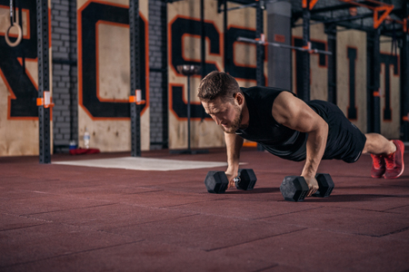 Handsome muscular man doing push ups on dumbbells in gym