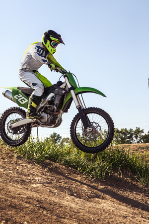Racer on dirt bike participates in motocross race, takes off and jumps on springboard