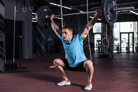 Young man at a crossfit gym lifting a barbell. Stock Photo