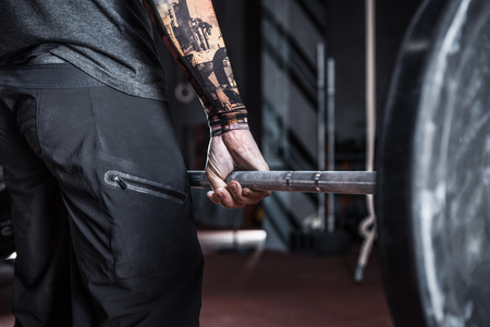 Closeup of athlete hand holding a barbell