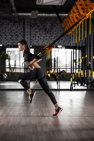 Beautiful fitness woman training with trx fitness straps. Suspension exercising in gym Stock Photo