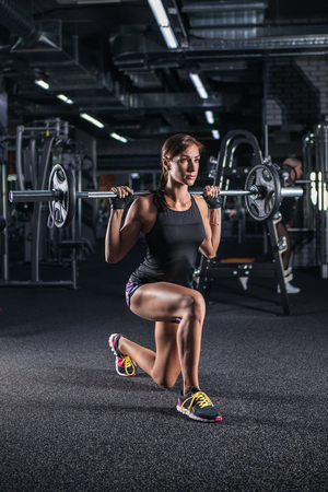 Sportive young woman in a gym training. Working out in a fitness gym. Stock Photo