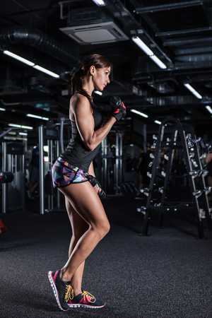 Muscular woman doing exercises with dumbbells at biceps.  Athletic fitness woman pumping up muscles with dumbbells.